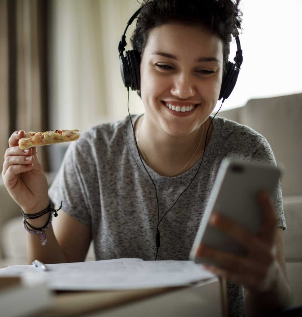 young woman eats pizza and talks to her online therapist on the phone. Cody higgs provides online therapy for women and teen girls in Tennessee.