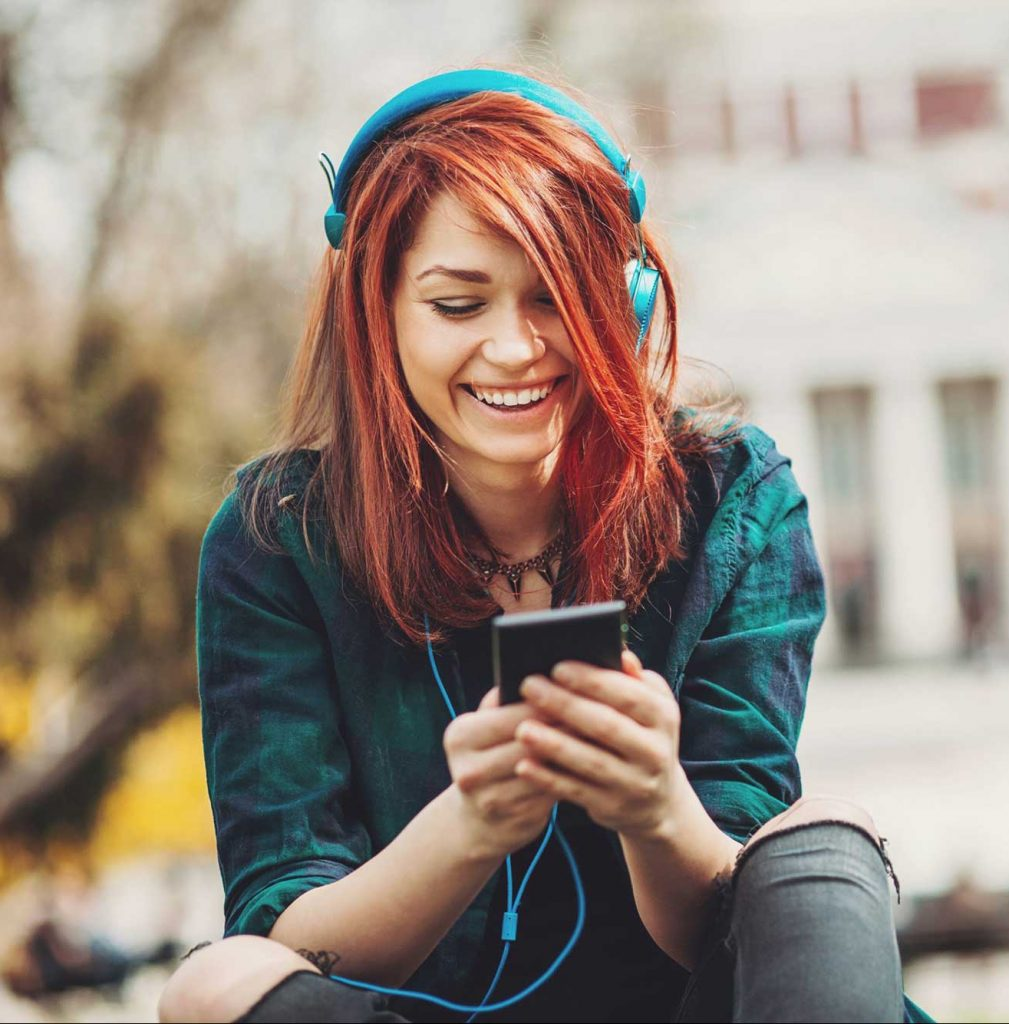 teen girl sits on her phone with headphones and gets anxiety treatment and depression treatment during online therapy in tennessee with cody higgs