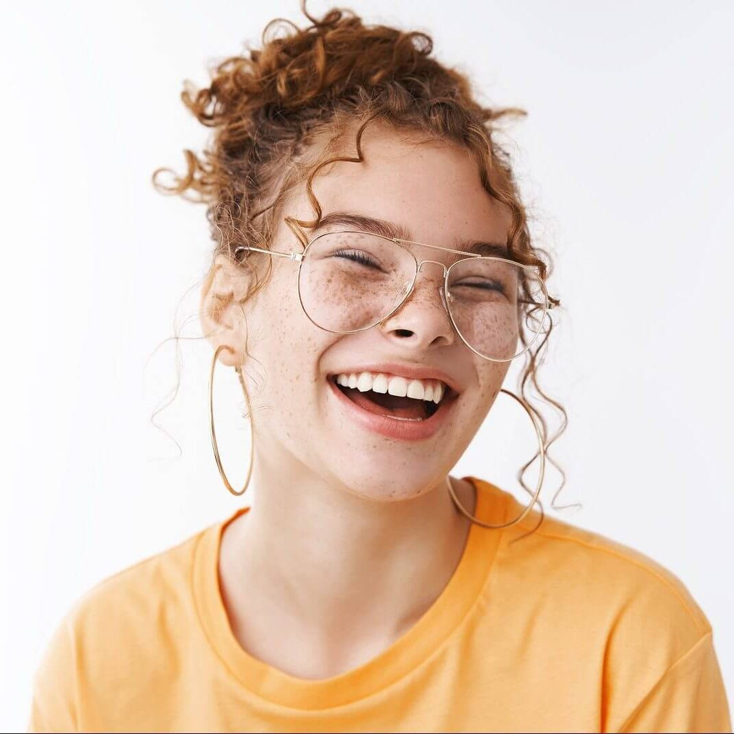 Cheerful teen girl in a yellow shirt smiles at the camera after teen counseling in franklin tn with teen therapist cody higgs 37067